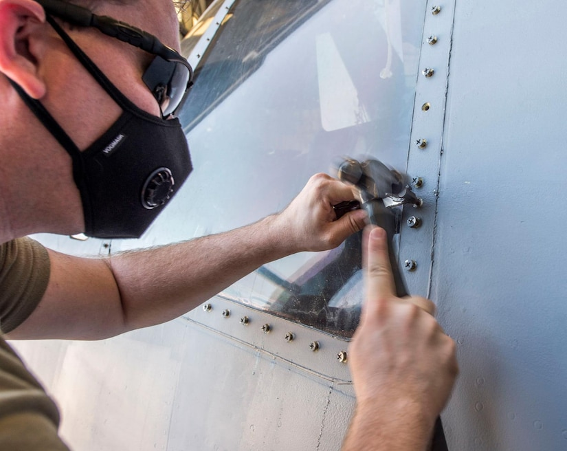 Senior Airman Spencer Coole, an aircraft structural maintenance journeyman assigned to the 437th Aircraft Maintenance Squadron, removes a stripped screw while replacing a window on the flightdeck of a C-17 Globemaster III aircraft at Joint Base Charleston, S.C., April 28, 2020. The 437th AMXS is still generating aircraft to support local training flights, missions from Air Mobility Command and supporting training for aeromedical evacuation personnel while being critically manned during the COVID-19 pandemic. The 437th AMXS is also implementing physical distancing when possible and following other Centers for Disease Control guidelines. Additionally, they have trained some of their personnel to decontaminate aircraft before and after missions to keep aircrews and 437th AMXS personnel safe. (U.S. Air Force Photo by Staff Sgt. Megan Munoz)