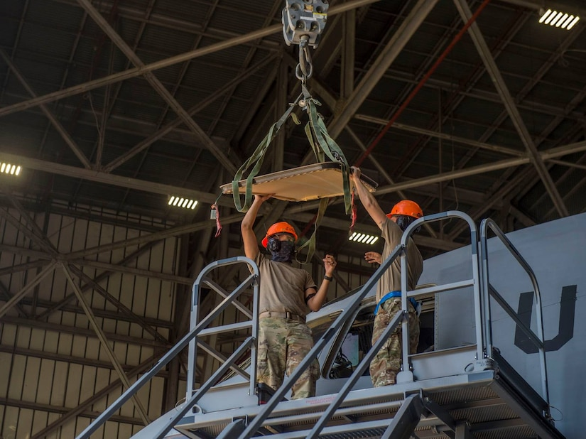 Staff Sgt. Eugino Rivas, left, and Senior Airman Sean McGrath, right, both crew chiefs assigned to the 437th Aircraft Maintenance Squadron, install a new window in the flightdeck of a C-17 Globemaster III aircraft at Joint Base Charleston, S.C., April 28, 2020. The 437th AMXS is still generating aircraft to support local training flights, missions from Air Mobility Command and supporting training for aeromedical evacuation personnel while being critically manned during the COVID-19 pandemic. The 437th AMXS is also implementing physical distancing when possible and following other Centers for Disease Control guidelines. Additionally, they have trained some of their personnel to decontaminate aircraft before and after missions to keep aircrews and 437th AMXS personnel safe. (U.S. Air Force Photo by Staff Sgt. Megan Munoz)