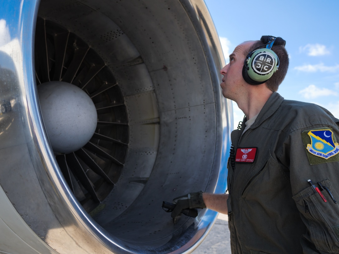 Photo shows a man with ear protection on looking into the parts of an aircraft.