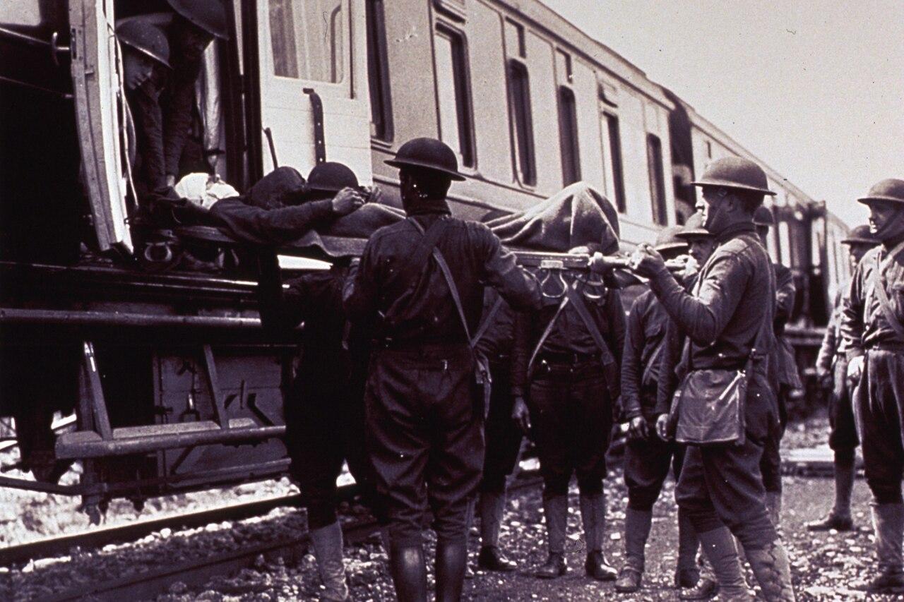 Troops load injured soldiers onto a World War I-era train