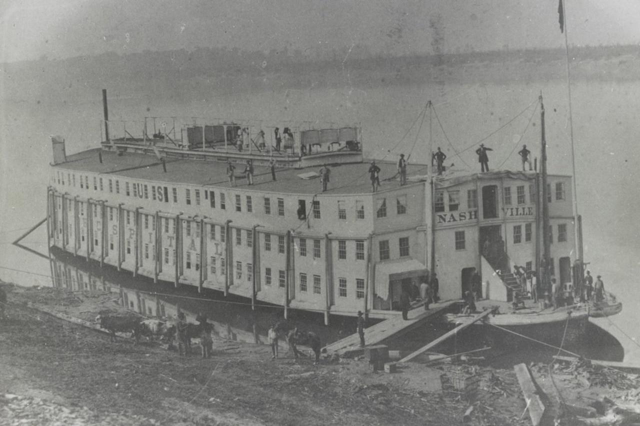 A Civil War-era steamship is docked along a river bank.