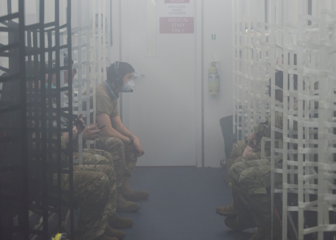 U.S. Airmen converse inside a Negatively Pressurized Conex prototype during in-flight testing on a C-17 Globemaster III, April 30, 2020. The NPC was rapidly developed and designed to fit inside both C-5 and C-17 aircraft to enable safe transport of up to 28 passengers, as well as teams of medical professionals to medical facilities around the globe. (U.S. Air Force photo by Staff Sgt. Chris Drzazgowski)