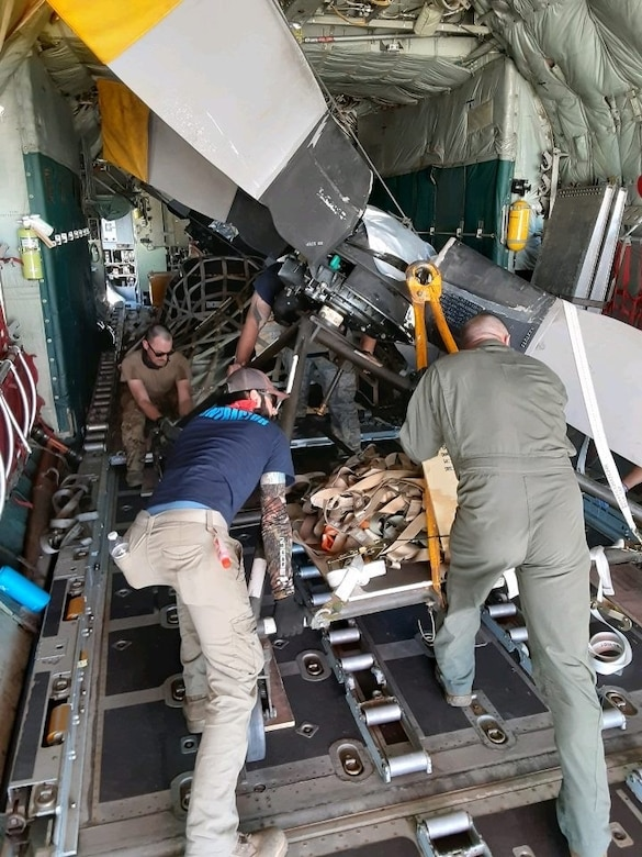 514th Flight Test Squadron aircrew and 309th Aerospace Maintenance and Regeneration Group personnel pushing a propeller in the back of an aircraft.
