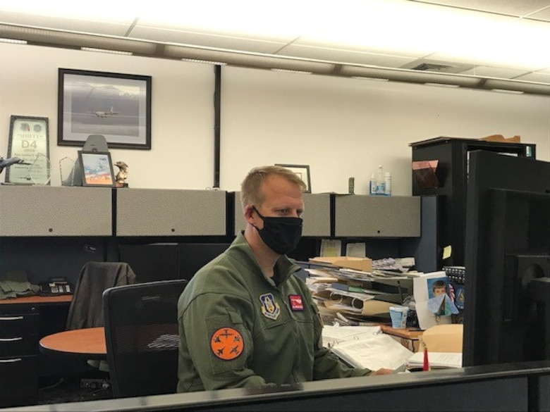 Maj. Jonathan Shiflett sitting at his computer desk wearing a face covering.