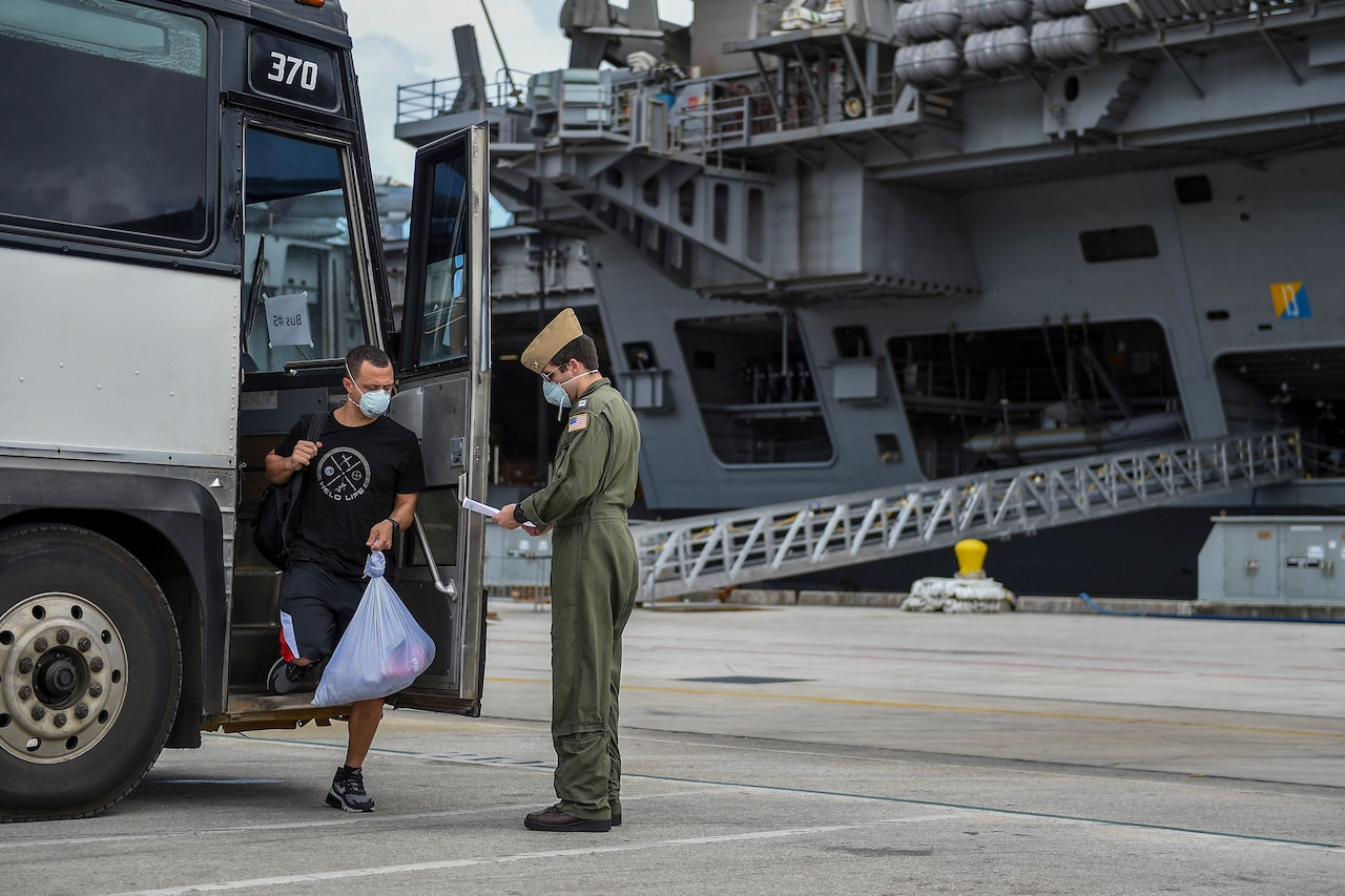 Sailor checks in with officer after getting off the bus. An aircraft carrier is in the background.