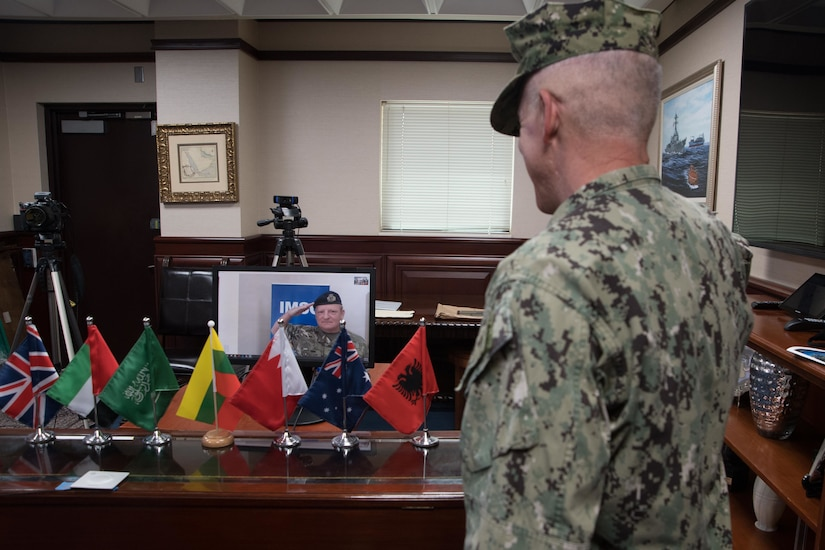 Admiral participates in a virtual change of command as a British naval officer is pictured live on a computer screen. Seven miniature national flags are on the table in front of the computer screen.