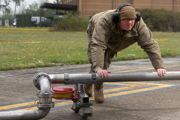 "Airman 1st Class Corey Purvis, a 48th Logistics Readiness Squadron fuels mobile distribution operator, pushes the mobile pantograph out to an F-15C Eagle for ""hot pit"" refueling operations at Royal Air Force Lakenheath, England, April 30, 2020. Continued ""hot pits"" during the COVID-19 pandemic provide necessary training and experience required to reduce the ground time between sorties by refueling active aircraft, enabling maximum training in a shorter time frame. (U.S. Air Force photo by Airman 1st Class Jessi Monte)"