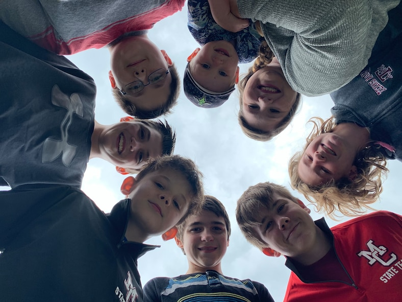 Six boys, aged 11 to 13 gather in a circle as they are photographed from below.