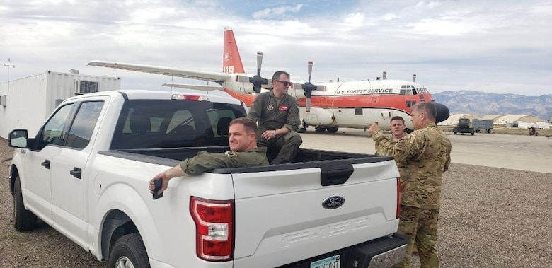 Aircrew sitting in and standing near the bed of a pickup truck.