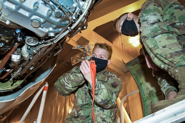Photo shows two Airmen wearing face masks working on rigging.