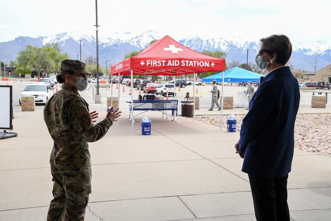 Secretary of the Air Force Barbara Barrett speaks with Maj. Emily Dietrich, 75th Medical Group, near a first aid station tent.