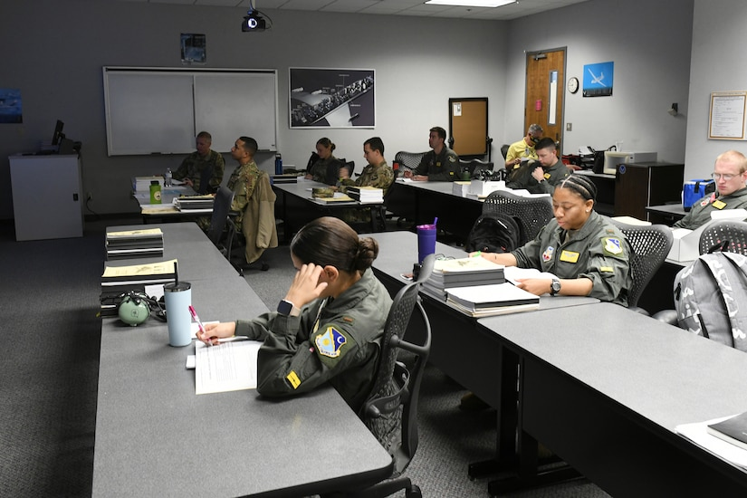 Photo shows multiple Airmen in a classroom setting reading notes at their tables.