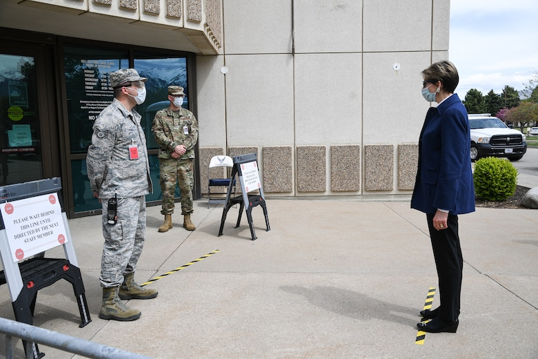 Secretary of the Air Force Barbara Barrett is screened by Staff Sgt. Ryan Thomas, 75th Medical Group, near the front doors of the medical clinic.