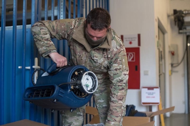 An Airman lifts an ion distribution unit out of a box.