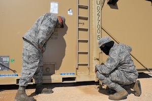 Tech. Sgt. Dieter Siegelin, 433rd Civil Engineer Squadron water and fuels systems maintenance craftsman, and Senior Airman LeAnthony Ashton, 433rd CES structures journeyman, check and adjust the level of a containerized shower and latrine facility April 30, 2020 at Joint Base San Antonio-Lackland.