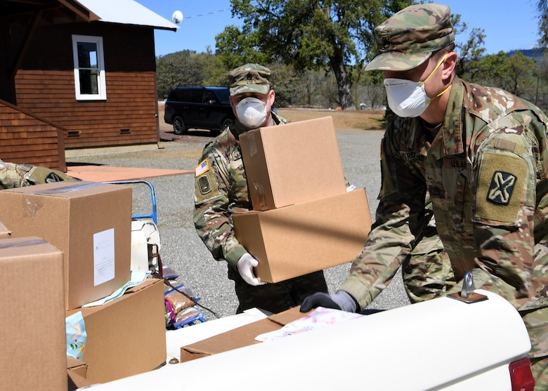 U.S. Army Staff Sgt. Joshua A. Mosley, left, and Staff Sgt. Chris Petrossian, both of the California Army National Guard's 115th Regional Support Group, load food items into a volunteer's truck to distribute to Napa Valley residents who are homebound during the COVID-19 crisis while working at Pope Valley Farm Center in St. Helena, California, April 1, 2020.