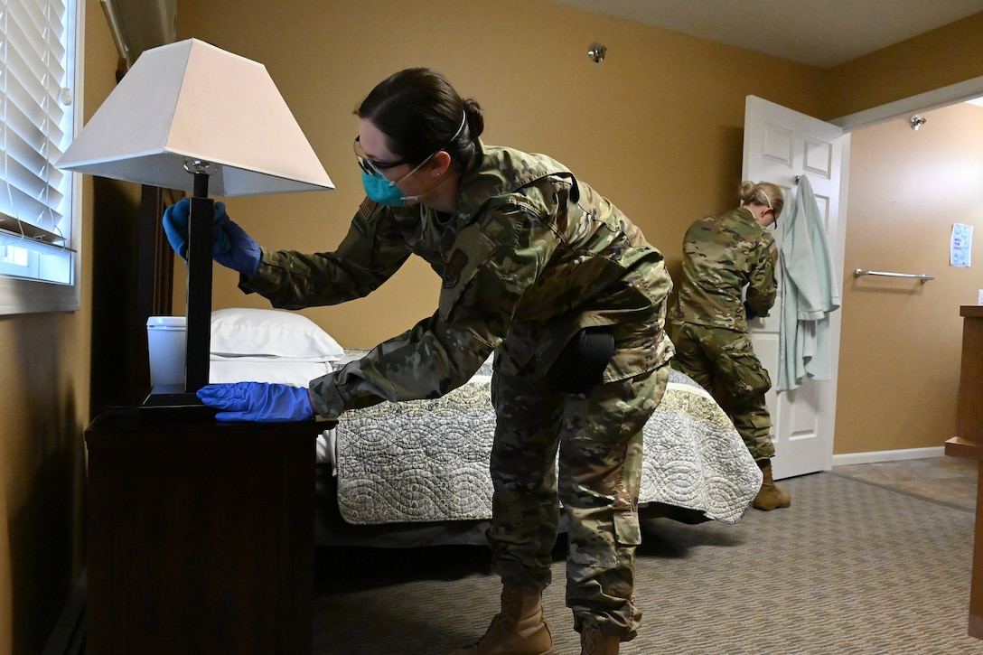 Photo of two Airmen cleaning the living area of an elderly resident of a congregate living center Fargo, N.D., May 1, 2020, The Airmen are wearing protective masks, glasses and gloves for safety.