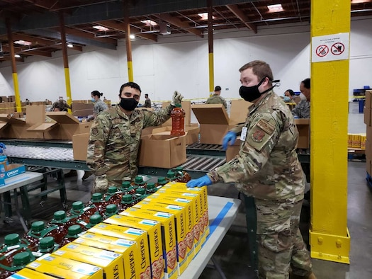 U.S. Air Force Staff Sgt. Matthew Bradley, left, and U.S. Air Force Staff Sgt. Jeremiah Jensen, right, both assigned to the 225th Air Defense Squadron, prepare food boxes at the Food Lifeline COVID Response warehouse April 23, 2020, in Seattle, Washington.  More than 250 Air and National Guardsmen are assigned to the warehouse where they are able to prepare, on average, 268 boxes an hour per line. (U.S. Air National Guard photo)