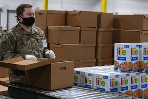 U.S. Air Force Staff Sgt. Jeremiah Jensen, assigned to the 225th Air Defense Squadron, prepares food boxes at the Food Lifeline COVID Response warehouse April 23, 2020 in Seattle, Washington.  More than 250 Air and National Guardsmen are assigned to the warehouse where they are able to prepare, on average, 268 boxes an hour per line. (U.S. Air National Guard photo by Master Sgt. Tim Chacon)