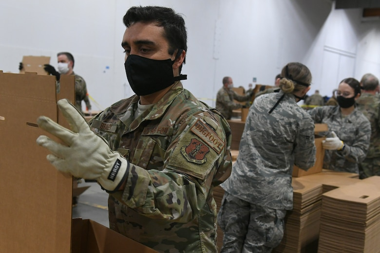 U.S. Air Force Staff Sgt. Matthew Bradley, assigned to the 225th Air Defense Squadron, prepares food boxes at the Food Lifeline COVID Response warehouse April 23, 2020, in Seattle, Washington.  More than 250 Air and National Guardsmen are assigned to the warehouse where they are able to prepare, on average, 268 boxes an hour per line. (U.S. Air National Guard photo by Master Sgt. Tim Chacon)