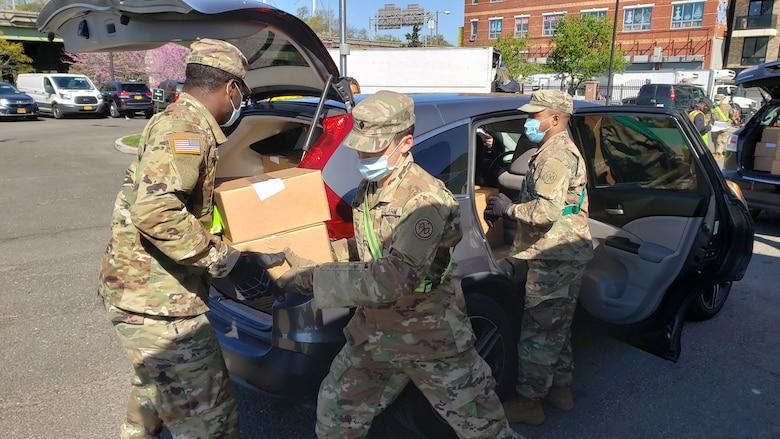 New York Army National Guard Soldiers, from left, Spc. Davier Weste, Spc. Cody Roche and Staff Sgt. Andre Hayden, assigned to the 1st Battalion, 258th Field Artillery, part of the 27th Infantry Brigade Combat Team, load cars with meals at the Queens Food Distribution Site May 2, 2020. The meals will be delivered to people who are quarantined and unable to go shopping.