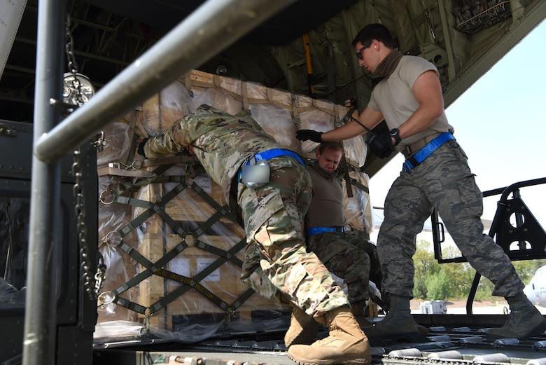 U.S. Airmen assigned to the 721st Aerial Port Squadron push cargo onto a C-130J Super Hercules aircraft.