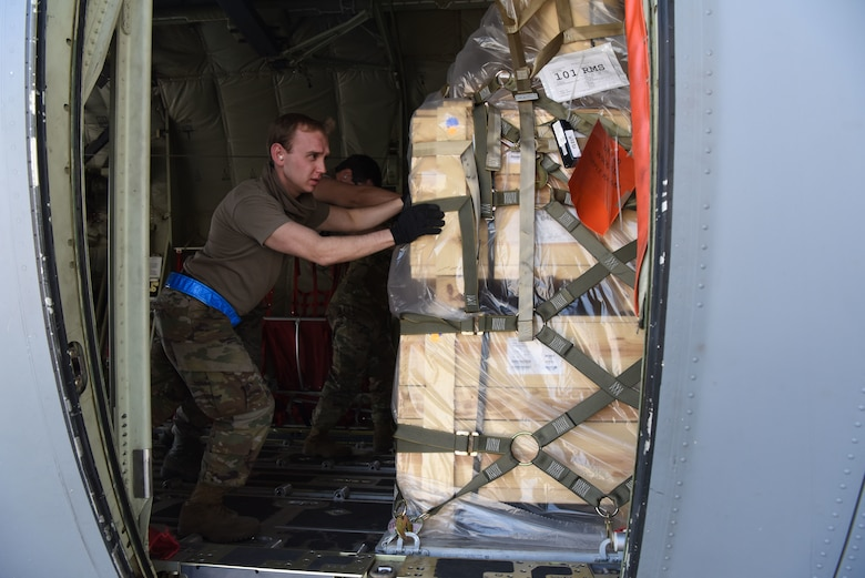 U.S. Air Force Staff Sgt. Ryan Hoback, 721st Aerial Port Squadron ramp supervisor, pushes cargo during a C-130J Super Hercules aircraft.