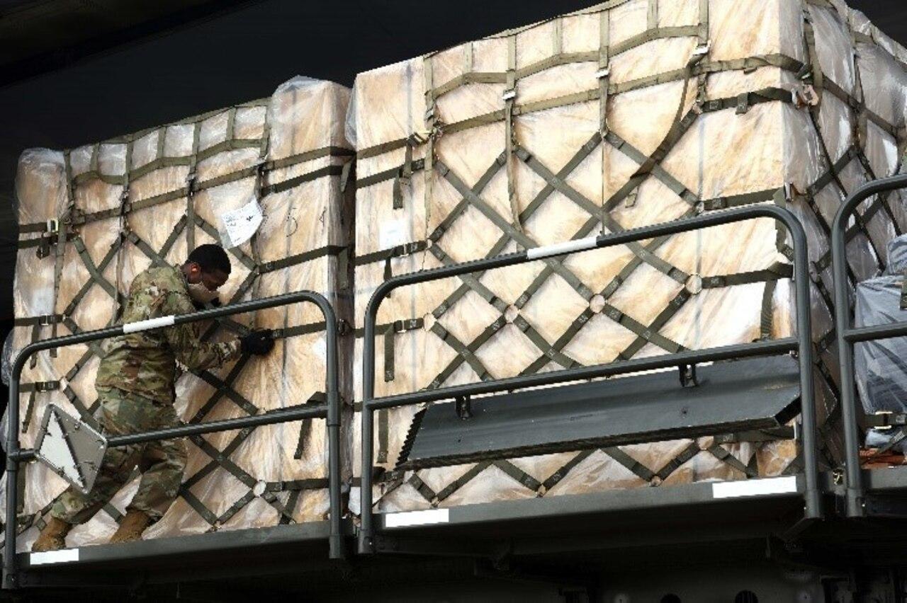 An airmen pushes pallets off a C-5 Super Galaxy.