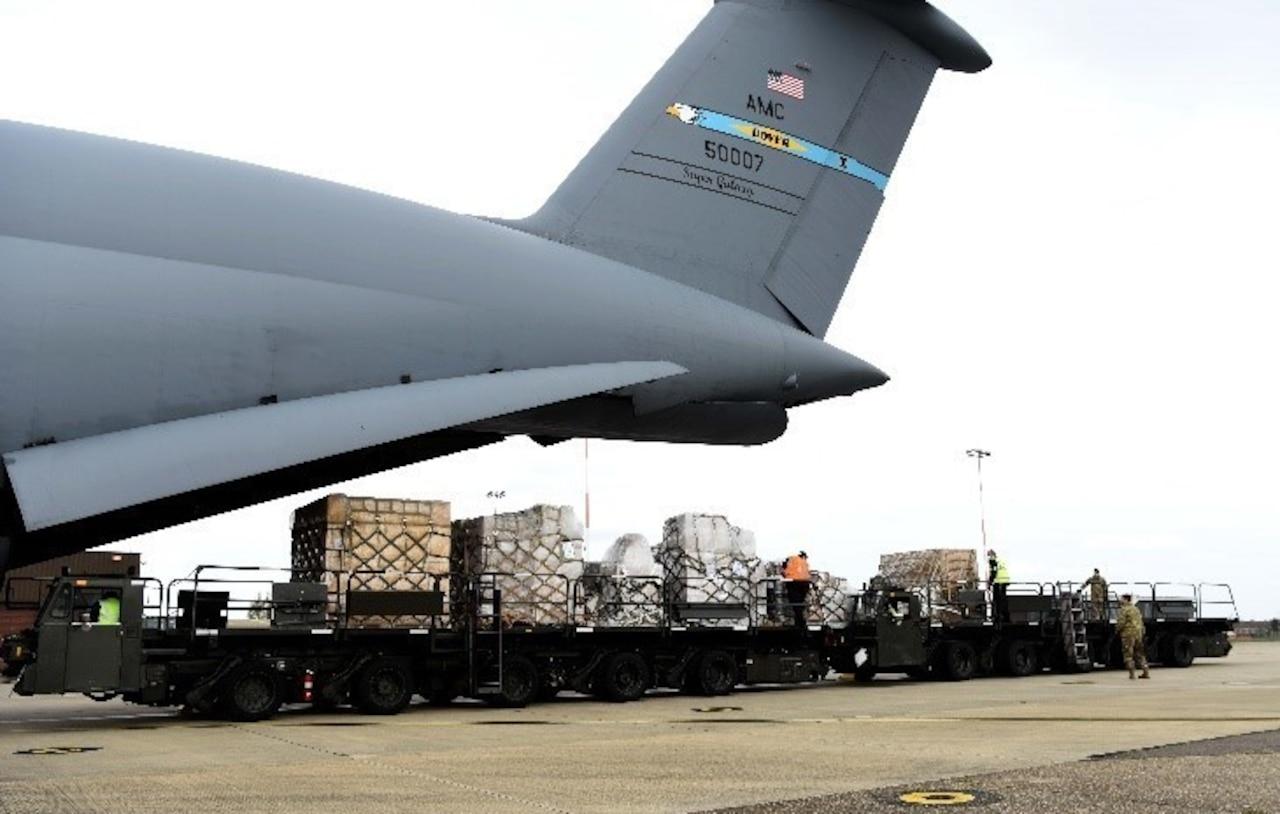 Airmen and contractors push pallets off a C-5 Super Galaxy.