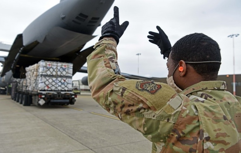 An airmen directs a K-loader loading pallets onto a C-5 Super Galaxy.