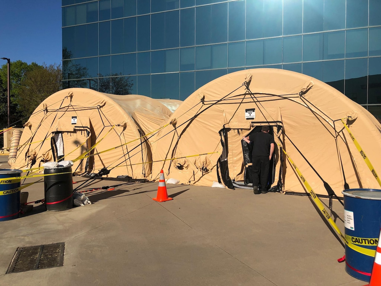 Military tents outside a hospital.