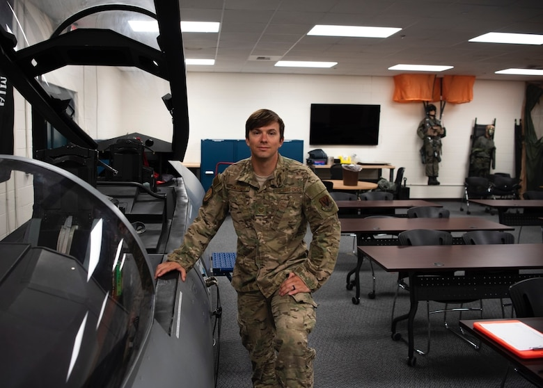 Tech. Sgt. Nicholas Cliché, 366th Operations Support Squadron air crew flight equipment lead trainer, posing with an F-15E evasion simulator, April 28, 2020, at Mountain Home Air Force Base, Idaho. As a Flight Equipment Trainer, Sgt. Cliché is accustomed to being ready for extreme situations. (U.S. Air Force photo by Airman 1st Class Gary Hilton)