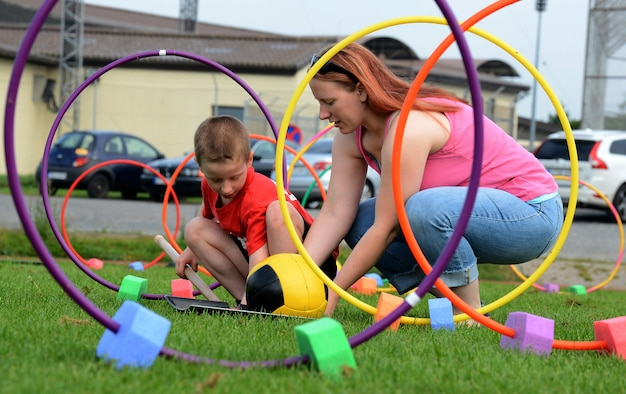 Mom and son manipulate outdoor play equipment