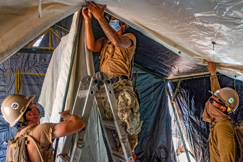 Sailors assembling a tent.