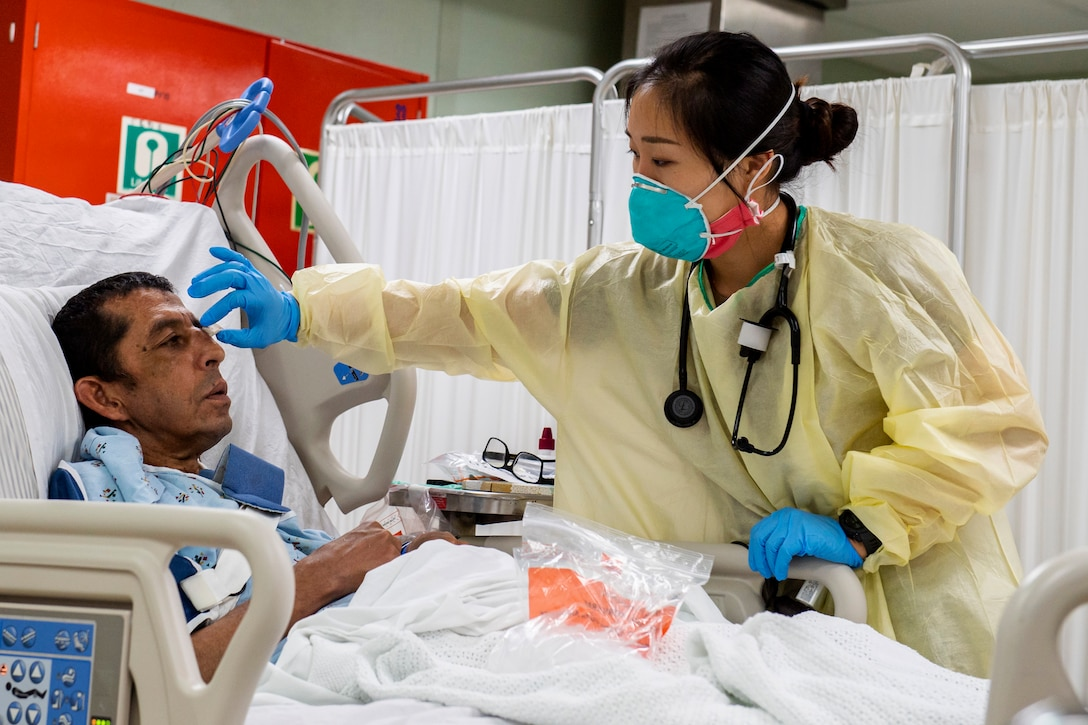 A medic in personal protective equipment removes a bandage from a bed-ridden patient's face.
