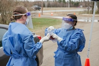 From left, Staff Sgt. Megan McMahon and Airman 1st Class Alyssa Berger of the 157th Medical Group collect a nasal sample May 1, 2020, at the Lancaster armory.