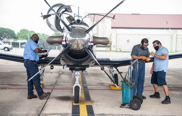 Larry Padilla, 12th Aircraft Maintenance Squadron, inspects the oil level reading of a T-6 Texan aircraft with Greg Garcia, 12th AMXS, at Joint Base San Antonio-Randolph April 7.