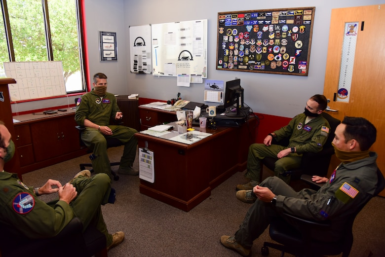"Lt. Col. Brian Tripp, 434th Flying Training Squadron director of operations, gathers with Capt. Joshua White, 434th FTS X flight commander and instructor pilot, and others for a meeting, April 23, 2020 at Laughlin Air Force Base, Texas. ""Just like much of the world we feel like we are all in this together, and we are prepared to do anything we can to help the instructor pilots and students,"" White said. ""As a flight commander my main concern right now is to take care of my instructors and students. If they feel like we don't care or if they are worried for their safety they will not be able to meet their full potential every day. We need them focused on safety and training."" (U.S. Air Force photo by Senior Airman Anne McCready)"