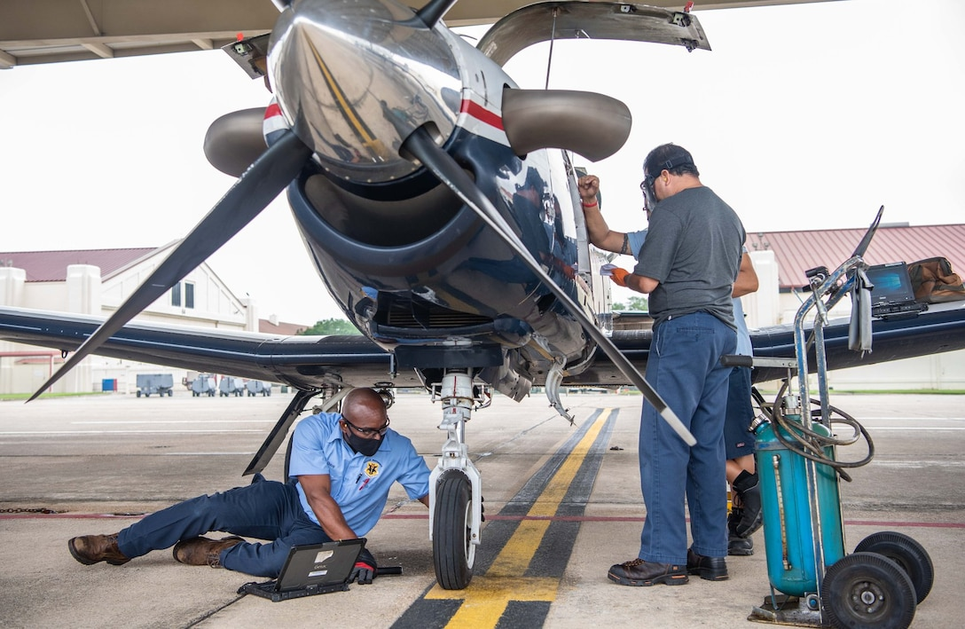 Shevon Vacianna, 12th Aircraft Maintenance Squadron, conducts routine maintenance by inspecting the front tire of a T-6 Texan aircraft at Joint Base San Antonio-Randolph April 7.