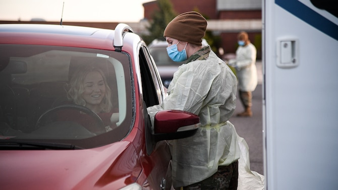 Senior Airman Amber Sansevieri, 75th Medical Group, interacts with a visitor during a drive-thru COVID-19 screening.