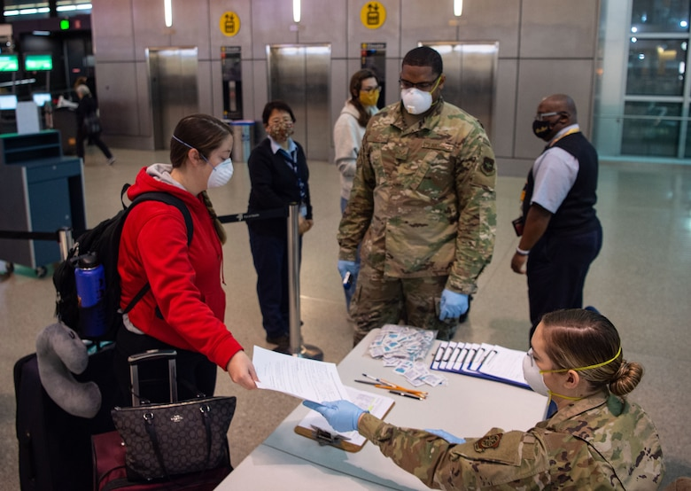 A passenger traveling to Asia, left, hands a medical questionnaire to Airman 1st Class Nicole Mourik, 62nd Aerial Port Squadron passenger service specialist, at the Seattle-Tacoma International Airport in Seattle, Wash., April 30, 2020. In order to travel while still preventing the spread of COVID-19, passengers must answer questions about their current health, where they have traveled recently, and whether they work in a medical facility. (U.S. Air Force photo by Senior Airman Tryphena Mayhugh)