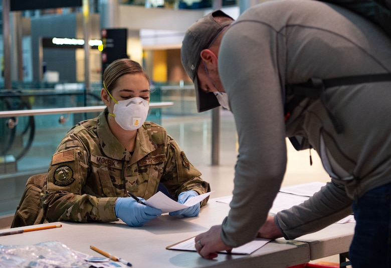 Airman 1st Class Nicole Mourik, 62nd Aerial Port Squadron passenger service specialist, checks the medical questionnaire paperwork for a passenger processing through the Air Mobility Command terminal at the Seattle-Tacoma International Airport in Seattle, Wash., April 30, 2020. The 62nd APS implemented a new medical screening process to ensure the safety of passengers and prevent the spread of COVID-19. (U.S. Air Force photo by Senior Airman Tryphena Mayhugh)