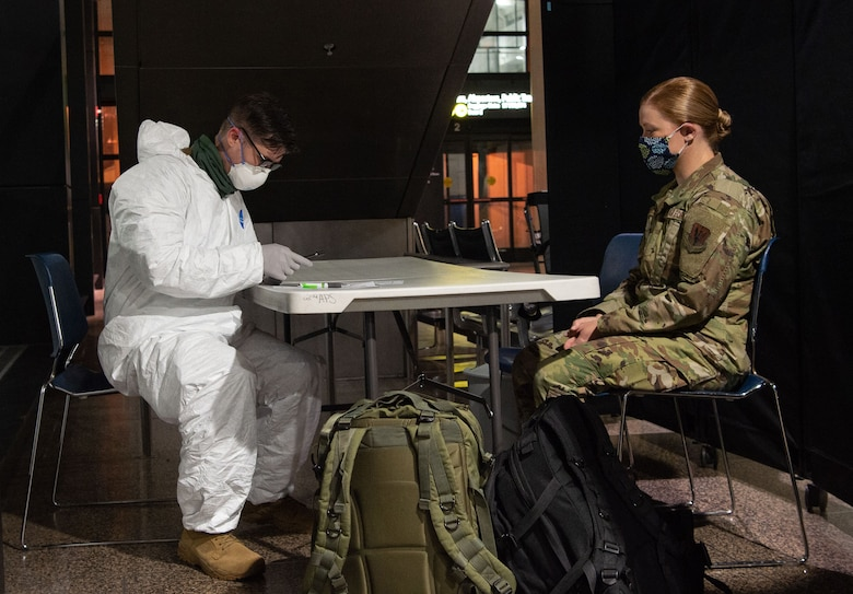 Staff Sgt. Benjamin Guris, 62nd Medical Squadron aerospace medical technician, left, conducts a secondary medical screening on a passenger traveling to Asia at the Seattle-Tacoma International Airport in Seattle, Wash., April 30, 2020. Secondary screenings are conducted for passengers who may be ill or work in a medical facility to ensure they have not contracted COVID-19. (U.S. Air Force photo by Senior Airman Tryphena Mayhugh)