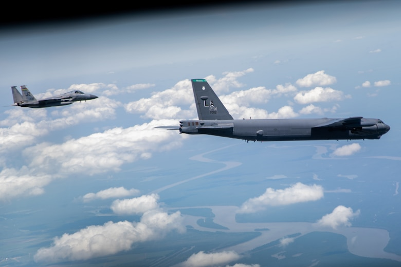 An F-15 Strike Eagle and B-52 Stratofortress fly over the Mississippi River