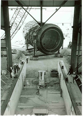 The first of two 550,000-pound test cell structures is pushed into the under construction Aeropropulsion Systems Test Facility building at Arnold Air Force Base in May 1980. The test cell was transported to the site on a 100,000-pound, 72-wheel transport frame specially constructed for the purpose. (U.S. Air Force photo)