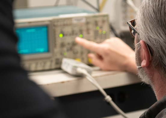 A PMEL technician points to a piece of calibration equipment
