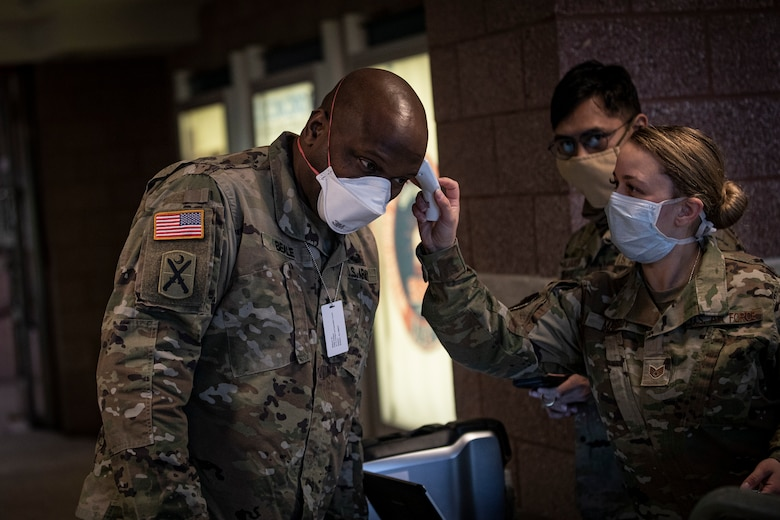 U.S. Army Brig. Gen. Jemal J. Beale, the Adjutant General of New Jersey, has his temperature taken by Air Force Staff Sgt. Samantha Massey at the entry control point for the Federal Medical Station inside the Atlantic City Convention Center, Atlantic City, N.J., April 21, 2020. The station was developed in conjunction with numerous organizations, including the FEMA, the U.S. Army Corps of Engineers, the Department of Health, the Office of Emergency Management, and the New Jersey National Guard. It is the third Federal Medical Station in the state, designed to ease the burden on local hospitals responding to the COVID-19 outbreak. (U.S. Air National Guard photo by Master Sgt. Matt Hecht)