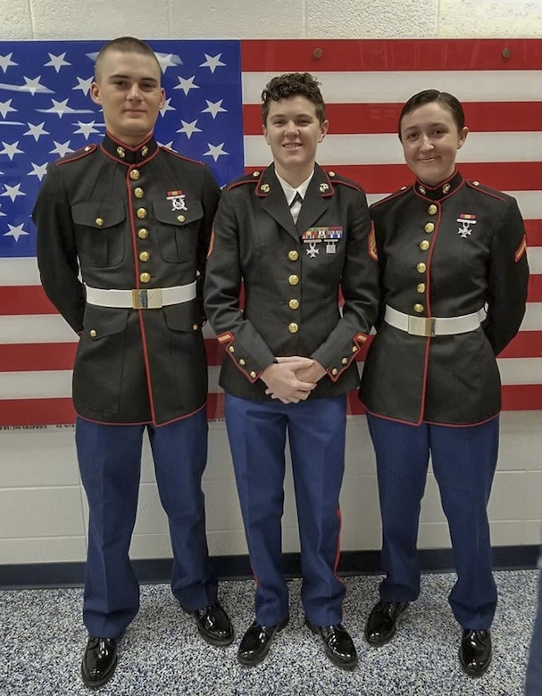 Staff Sgt. Mallory Kirk poses for a photo during a high school visit with two recently graduated Marines. Kirk is a recruiter with Recruiting Substation Mobile, AL.