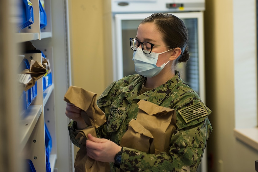 Hospitalman Seaman Apprentice Gianna Tamburro, assigned to the Naval Medical Readiness Training Command, organizes prescriptions alphabetically according to the names of patients at the Naval Health Clinic Charleston Pharmacy at Joint Base Charleston, S.C., April 24, 2020. The NHCC Pharmacy altered their customer service operations to have the primary way to obtain a prescription be through the drive-thru. Pharmacy personnel are protecting patients and themselves by washing their hands every 30 mins, practicing physical distancing, wearing masks and cleaning routinely.