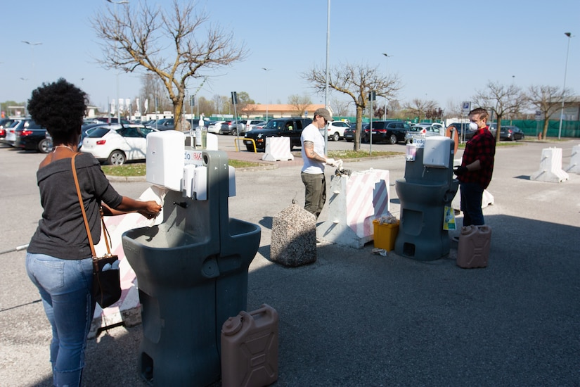 People wash their hands at portable hand washing stations.